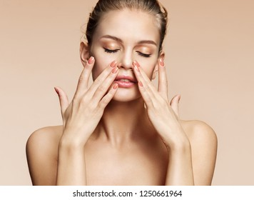 Beautiful woman doing facial massage, touching her face. Photo of woman with clean healthy skin on beige background. Skin care and beauty concept
