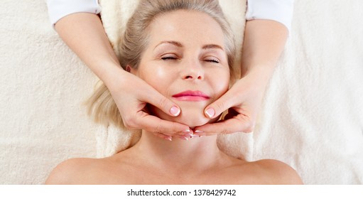 beautiful woman doing facial massage in a spa salon. selective focus.