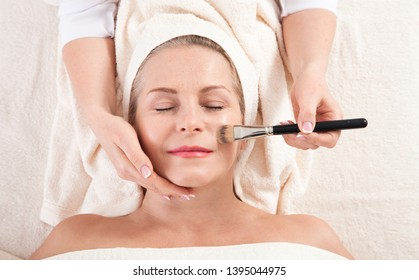 beautiful woman doing facial massage in a spa salon. selective focus.