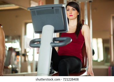 Beautiful woman doing her daily fitness excercises on stationary bycicle at the gym.