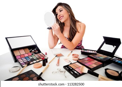 Beautiful woman doing her makeup - isolated over a white background