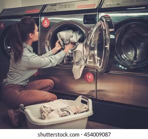 Beautiful woman doing laundry at laundromat shop.