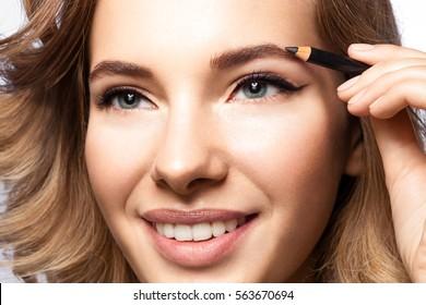 Beautiful woman doing makeup eyebrow pencil