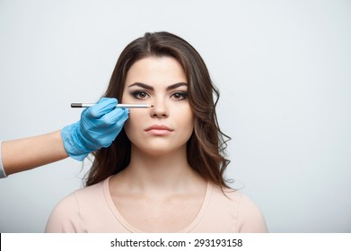 Beautiful woman is doing make-up. She is sitting and looking straight seriously. Female hand is raising black pencil to her nose. Isolated on a grey background and there is copy space in the right