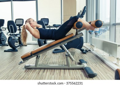 Beautiful woman doing press fitness exercise at sport gym.