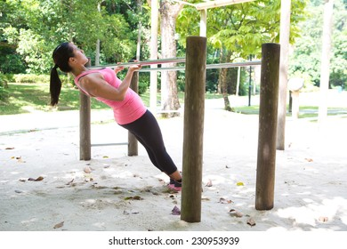 Beautiful woman doing pull up on exercise bar in a park