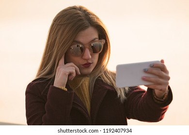 Beautiful woman doing selfie with cellphone outdoors.