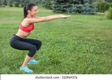 Beautiful woman is doing squats in park. She is stretching her arms forward. The sportswoman is smiling happily. Copy space in right side