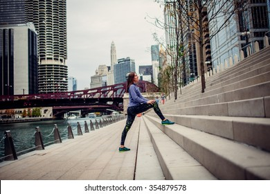 Beautiful woman doing stretching exercise in the city