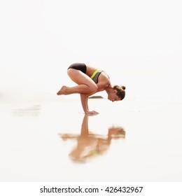beautiful woman doing yoga balance on beach.