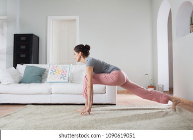 Beautiful woman doing yoga at home, training fitness sport, mindfulness, living room interior. Healthy female stretching legs, spiritual meditation exercises, indoors. Well being recreation lifestyle.