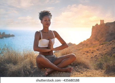 Beautiful woman doing yoga on a cliff, behind an amazing sunset in the sea