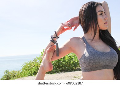 Beautiful woman doing yoga outdoors while wearing mala prayer beads.