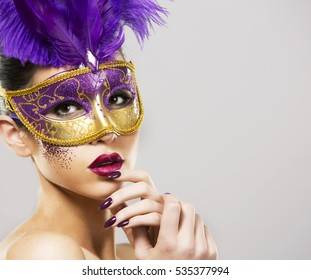 beautiful woman with dramatic mekaup and pruple lipstick wearing puprle mask. Light background. Golden.