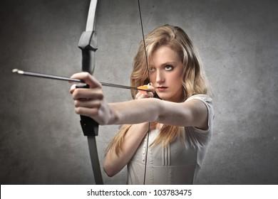 Beautiful woman drawing a bow