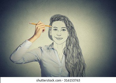 beautiful woman drawing self portrait face, hiding true emotion isolated on grey wall background. Private life, identity concept.