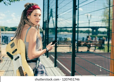 Beautiful woman with dreadlocks looking relaxed and turning her head while being outdoors with modern device and her smartphone