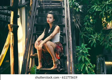 Beautiful woman with dreadlocks sitting on the stairs of her jungle huts