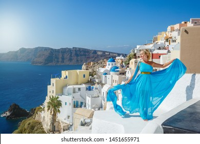 Beautiful woman in dress against  sea and architecture of Santorini island, Greece