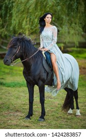 beautiful woman in dress with black horse in nature.