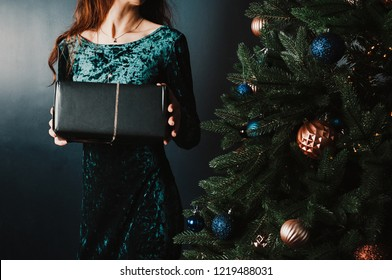 Beautiful woman in a dress holding a gift box near Christmas tree. New Year and Christmas concept. Luxury green, blue, golden colors. Home and family warmth