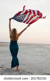 Beautiful woman in dress holds American flag above head while standing on beach