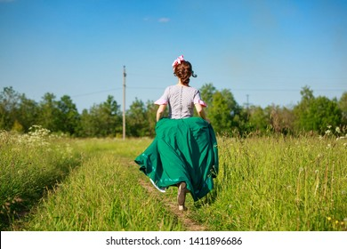 beautiful woman in dress in nature running on the road.