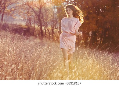 Beautiful woman in dress runing in the autumn forest