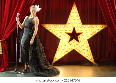Beautiful woman dressed as bat performing on red stage