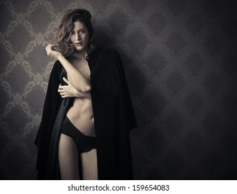 beautiful woman dressed with black cape and sexy underpants