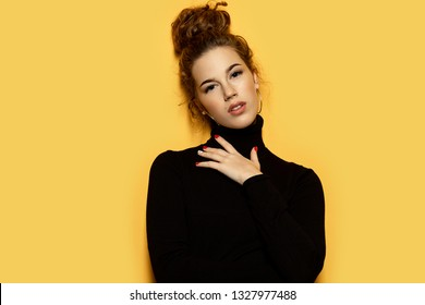 Beautiful woman dressed in black on yellow background. Pretty model dressed in stylish black pullover. Trend and lifestyle concept