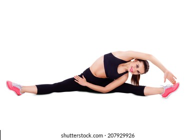 Beautiful woman dressed for fitness doing stretching exercises