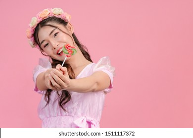 A beautiful woman dressed in a pink princess is playing with her sweet candy on a pink background.