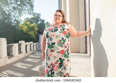 Beautiful woman dressed in summer dress  and glsses walking outdoor in the street of the city . Style overweight girl outdoor.