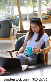 Beautiful woman drink coffee and play internet at cafe