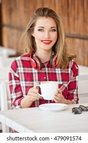 Beautiful woman drinking cappuccino coffee in the summer outdoor cafes.