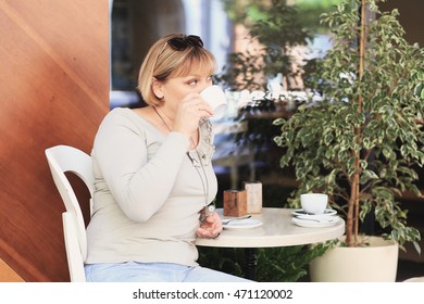Beautiful woman is drinking coffee in the cafe. She has got blonde hair, green eyes, white skin.