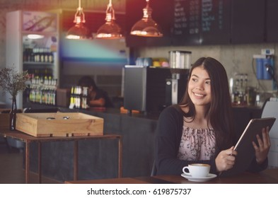 Beautiful woman drinking coffee in cafe .