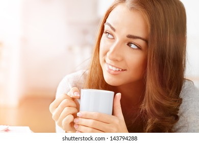 Beautiful woman drinking coffee at home