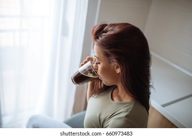 Beautiful woman drinking coffee and looking through the window.