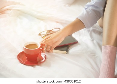 Beautiful woman drinking coffee on bed, in the morning.