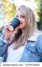 Beautiful woman is drinking coffee outside in the city