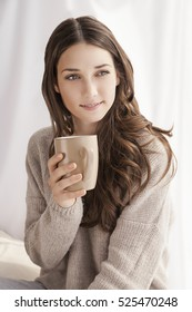 beautiful woman drinking coffee, sitting by window
