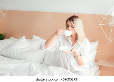 Beautiful woman drinking a coffee sitting on her bed home