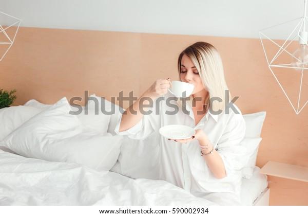 ベッドの家に座ってコーヒーを飲む美しい女性