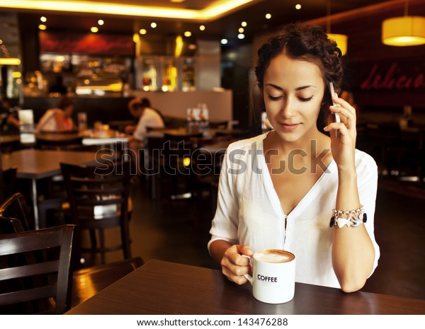 Beautiful Woman Drinking Coffee and talking on cellphone