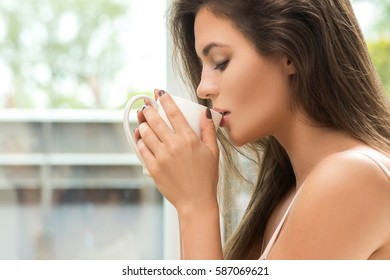 Beautiful woman drinking coffee or tea at the morning