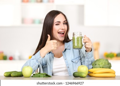 Beautiful woman drinking fresh smoothie in the kitchen