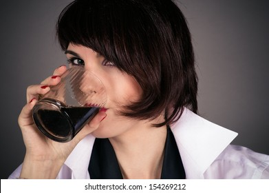 beautiful woman is drinking a glass of whiskey