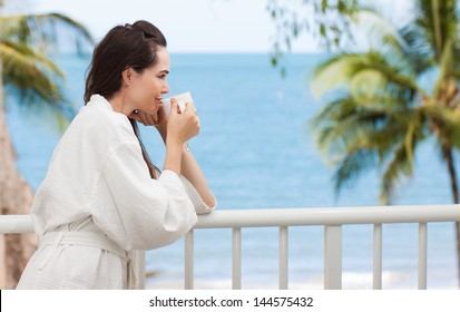 Beautiful woman drinking her morning coffee or tea on a tropical balcony.